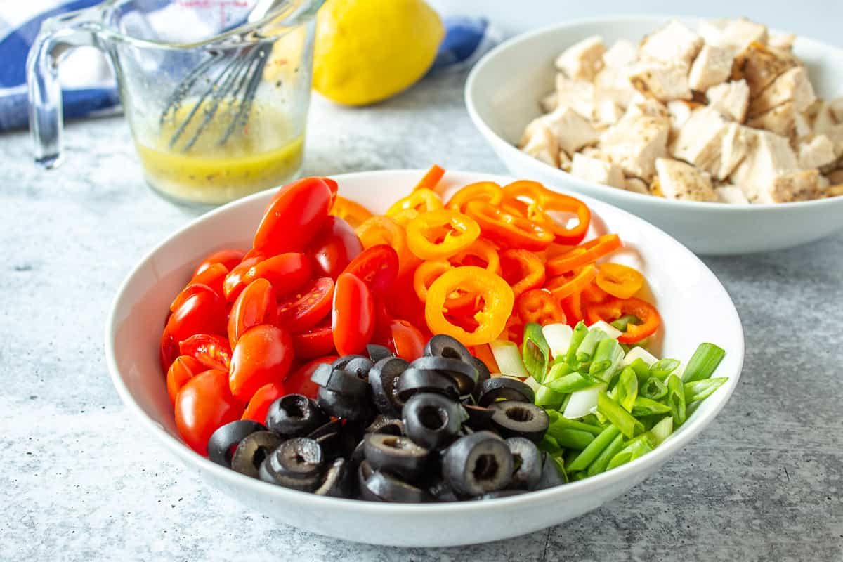 Fresh cut peppers, tomatoes and onions in a white bowl.