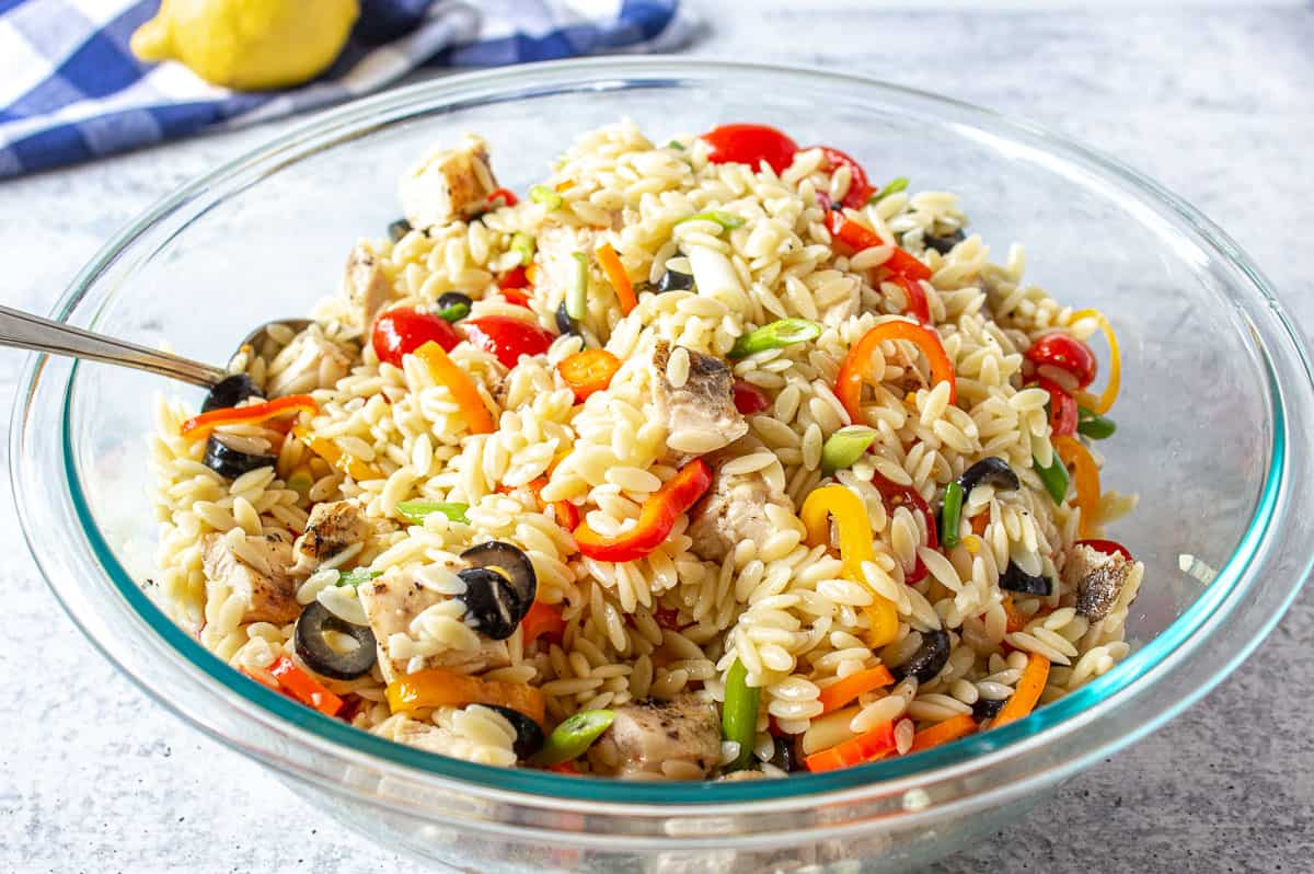 Orzo mixed with fresh veggies and black olives in a large glass bowl.