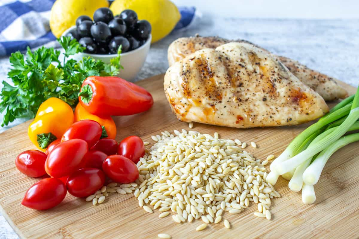 Dried orzo pasta on a cutting board along with fresh vegetables and a grilled chicken breast.