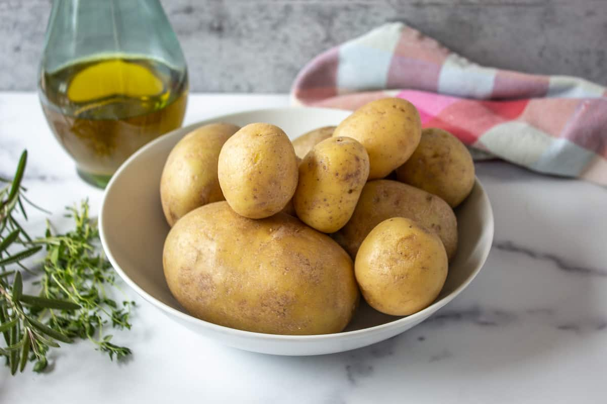 A bowl of different sized yukon potatoes.