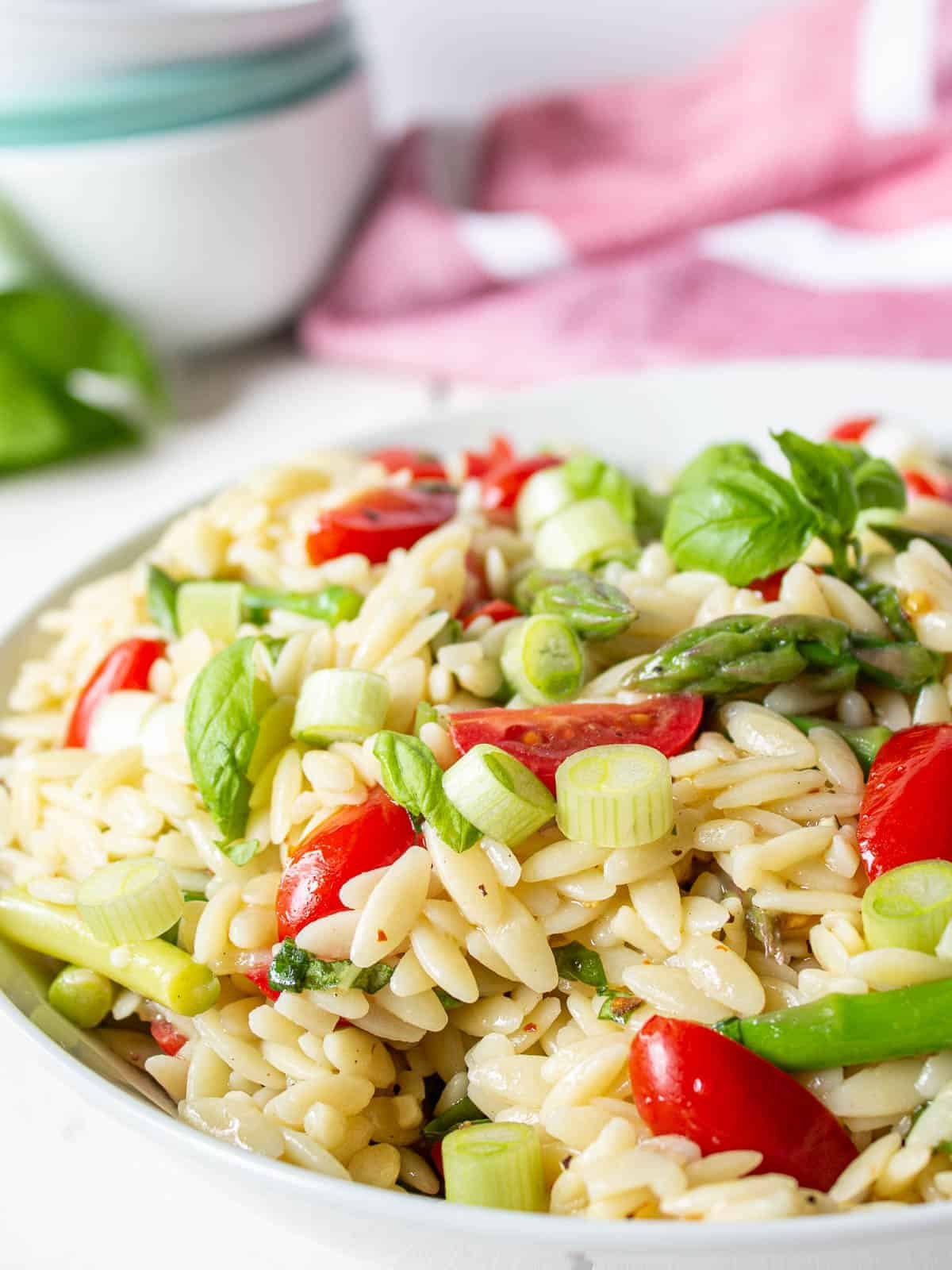Orzo pasta with chopped asparagus and cherry tomatoes in a white bowl.
