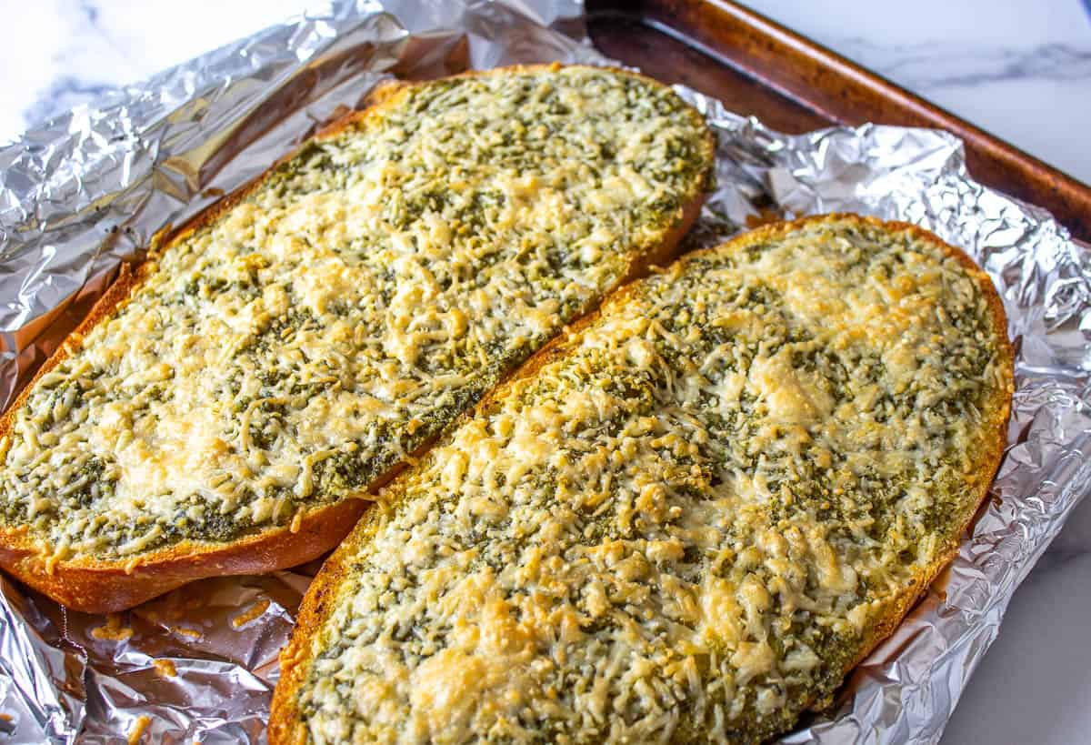 Cheesy garlic bread on top of foil on a baking sheet.