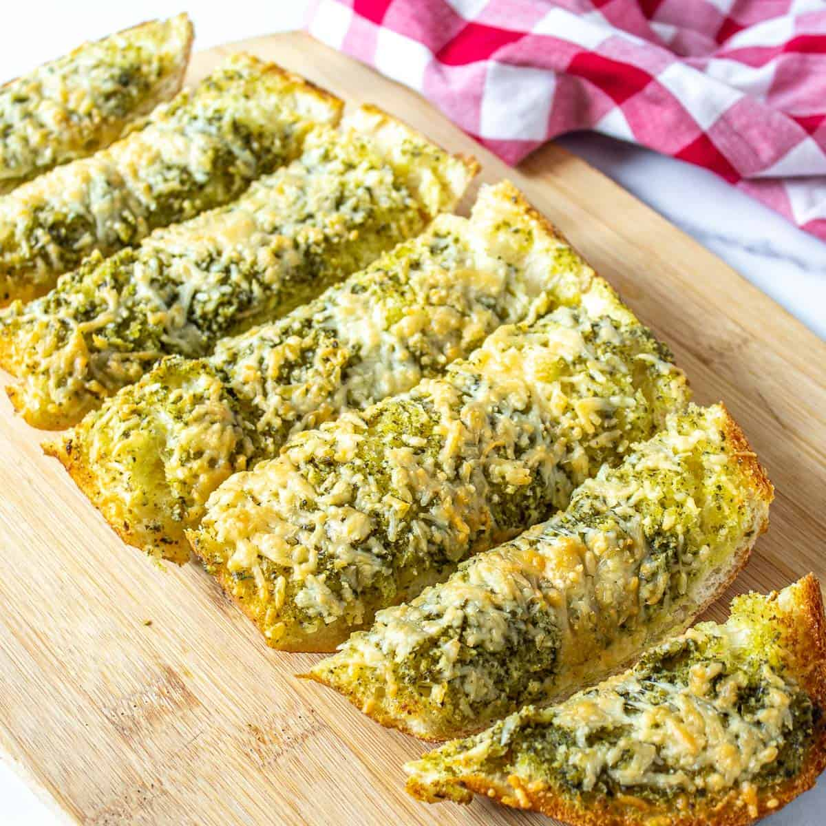Slices of french bread topped with pesto and cheese.