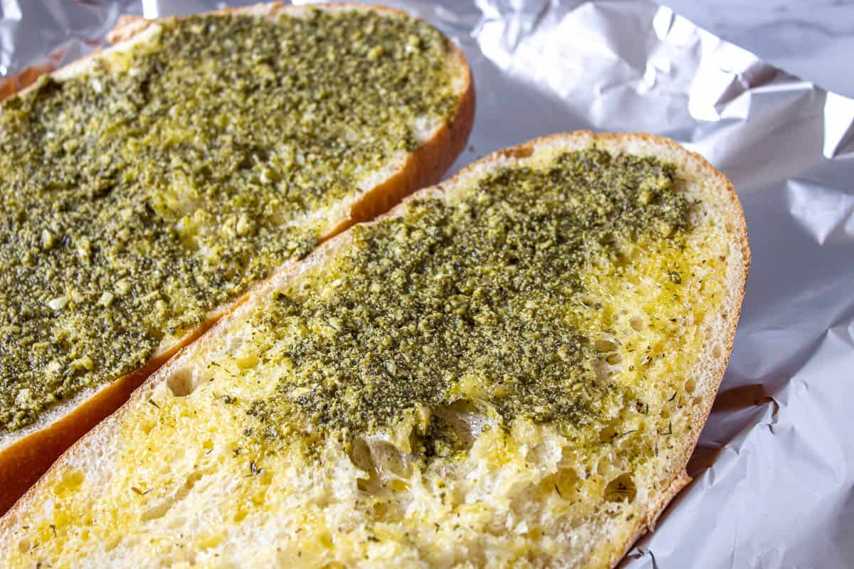 Sliced french bread topped with butter and pesto.