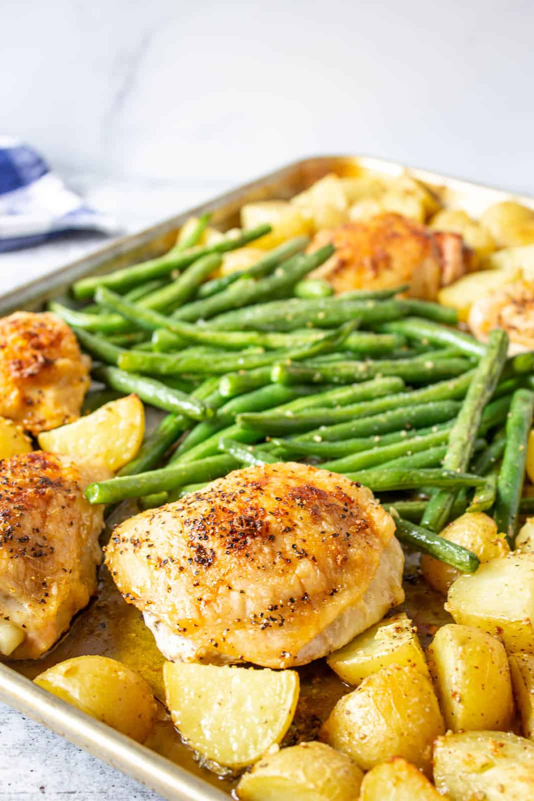 A sheet pan filled with baked chicken, potatoes, and green beans.