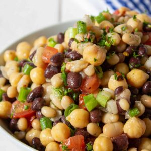 Black beans, and garbanzo beans mixed with tomatoes and green onions in a bowl.
