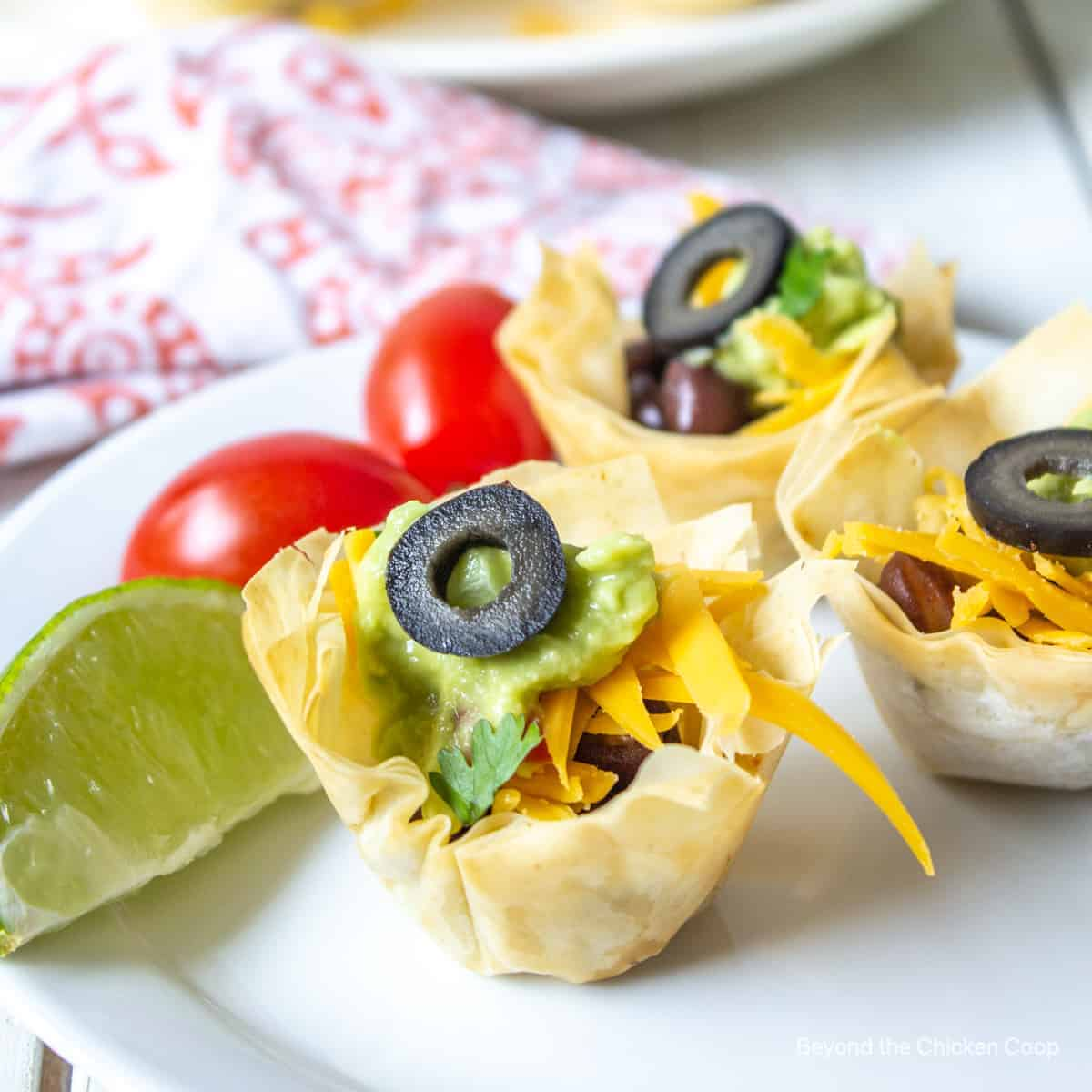Crispy mini cups filled with black beans, cheese and guacamole and topped with a black olive.