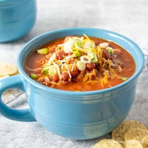 A blue mug filled with chili topped with cheese and green onions.