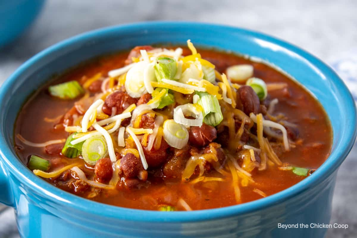 A bowl of chili with beans topped with onions and cheese in a blue bowl.