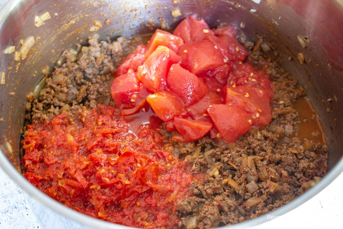 Chopped tomatoes and tomato sauce on top of cooked burger.