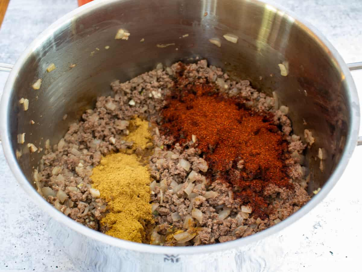 Ground chili powder and ground cumin added to cooked burger.