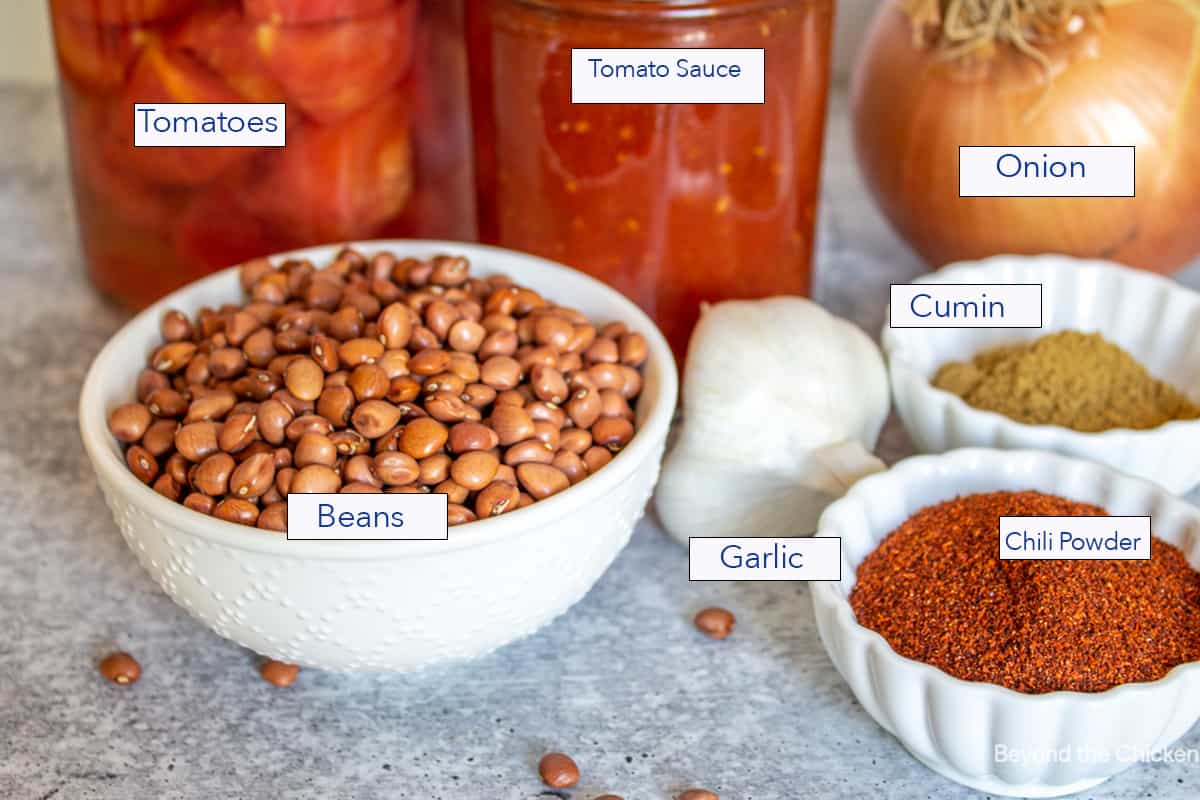 Small white bowls filled with dried beans, seasoning and jars filled with tomatoes.