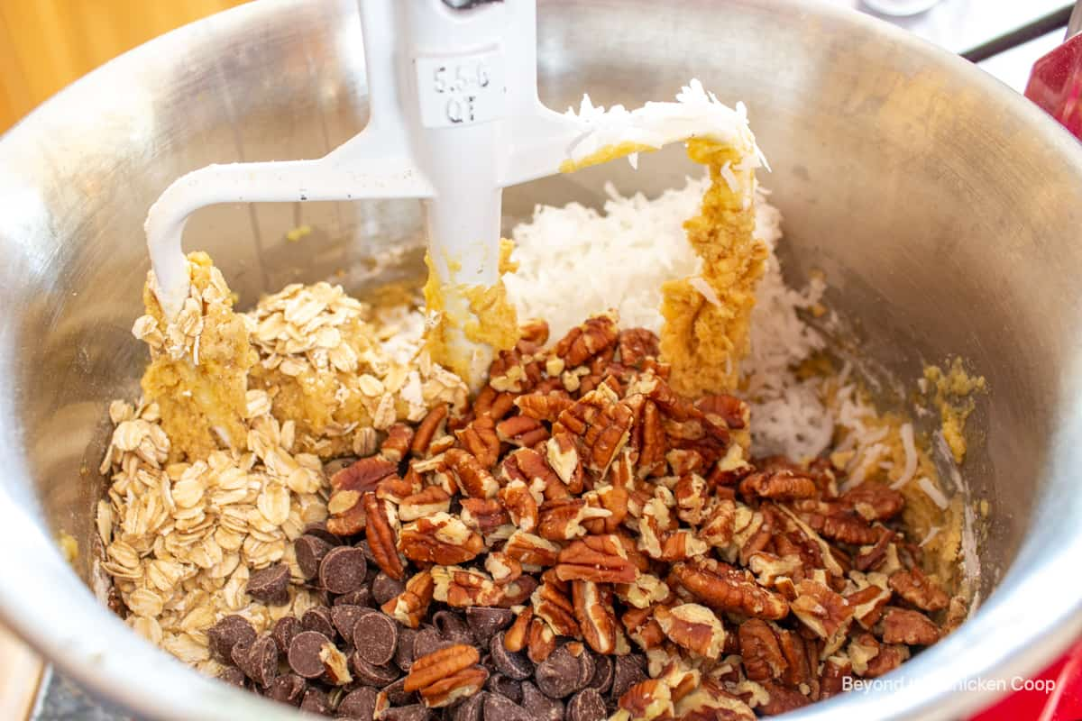 A mixing bowl filled with cookie dough, pecans, chocolate chips, coconut and oats.