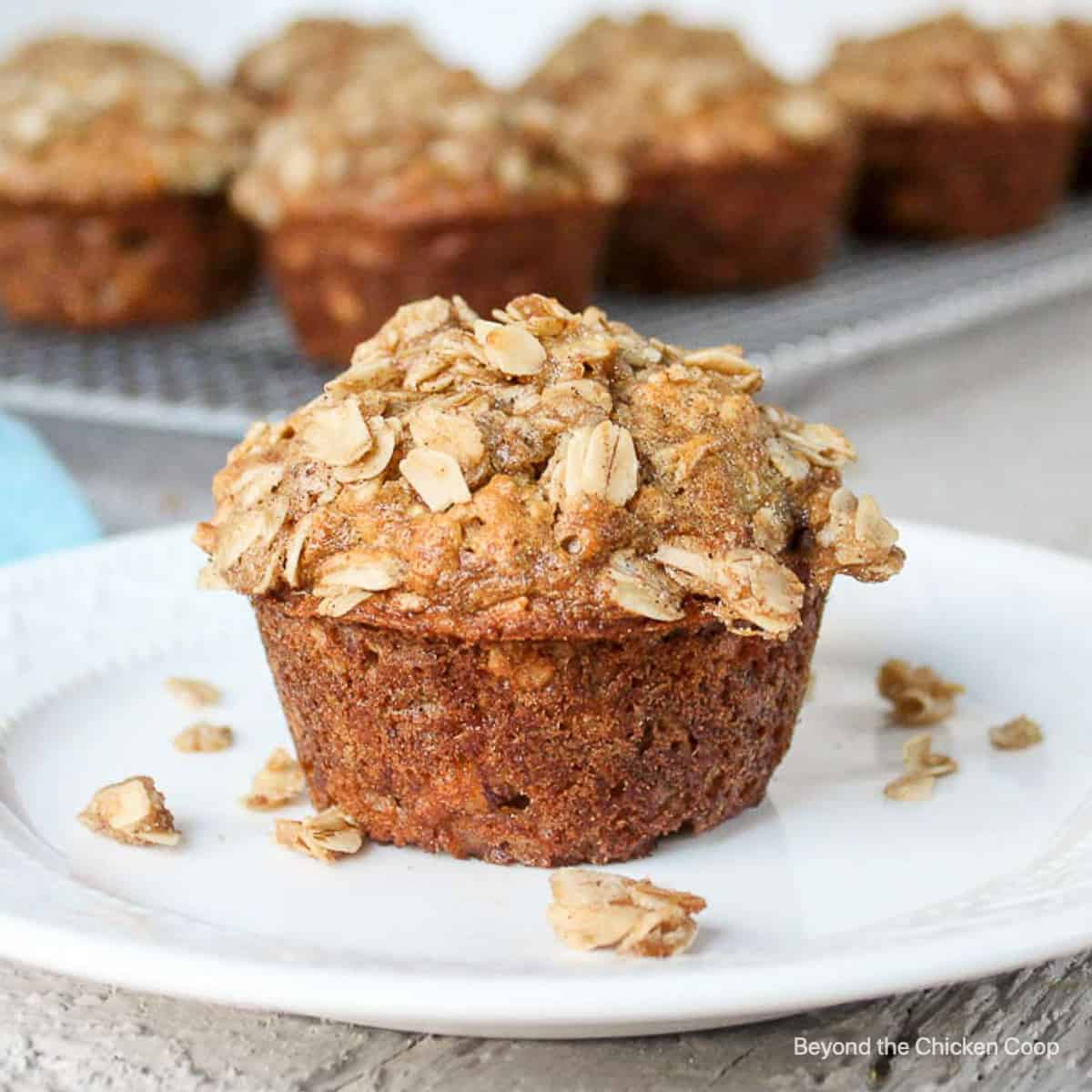 A single muffin topped with a crumbly topping on a plate.