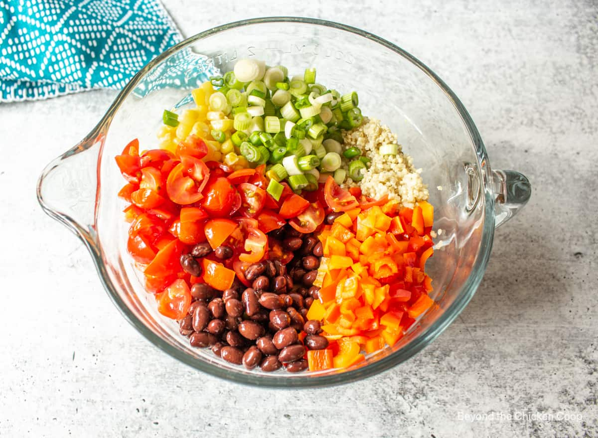 Chopped tomatoes, peppers, black beans and green onions in a glass bowl.