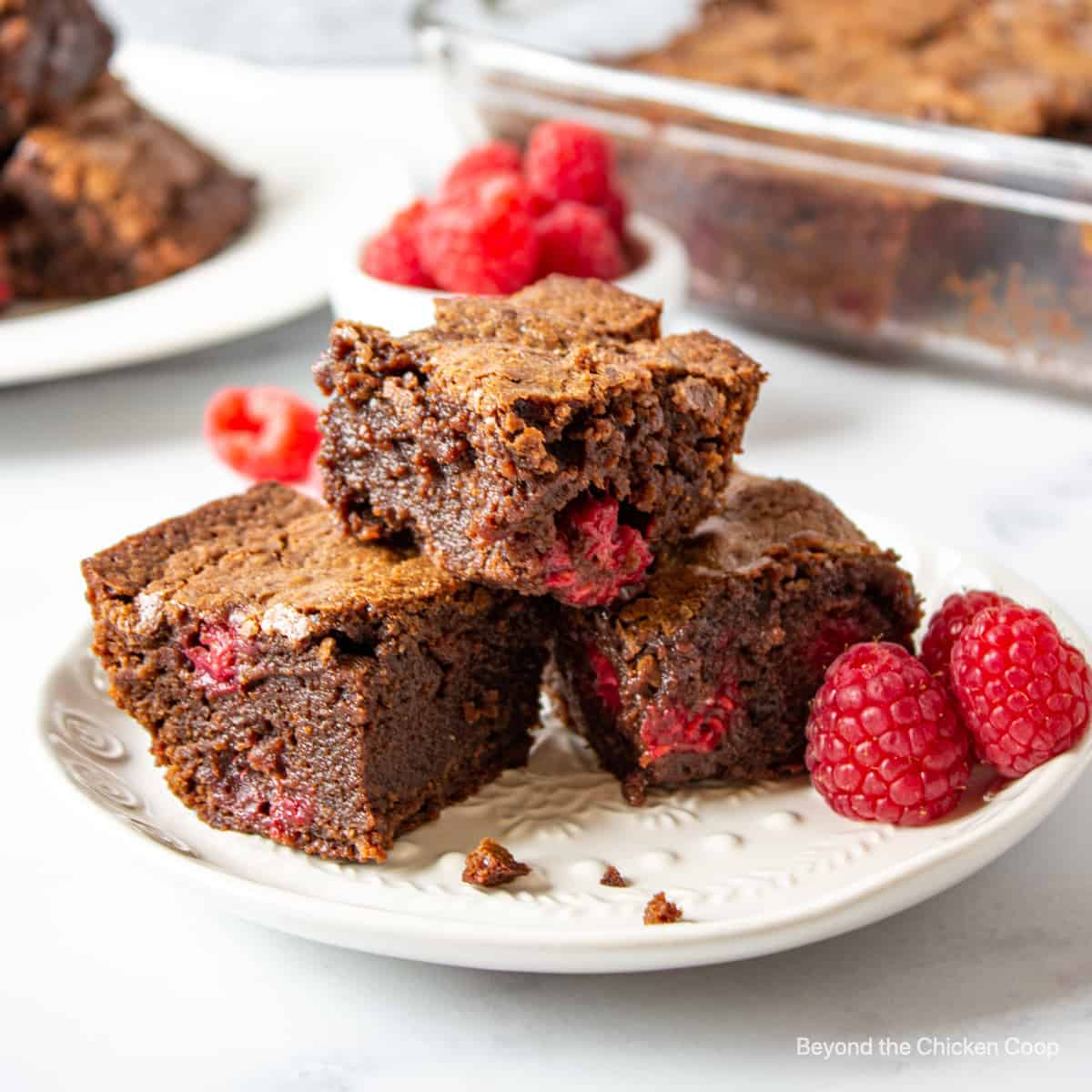 Three brownies filled with raspberries on a white plate.