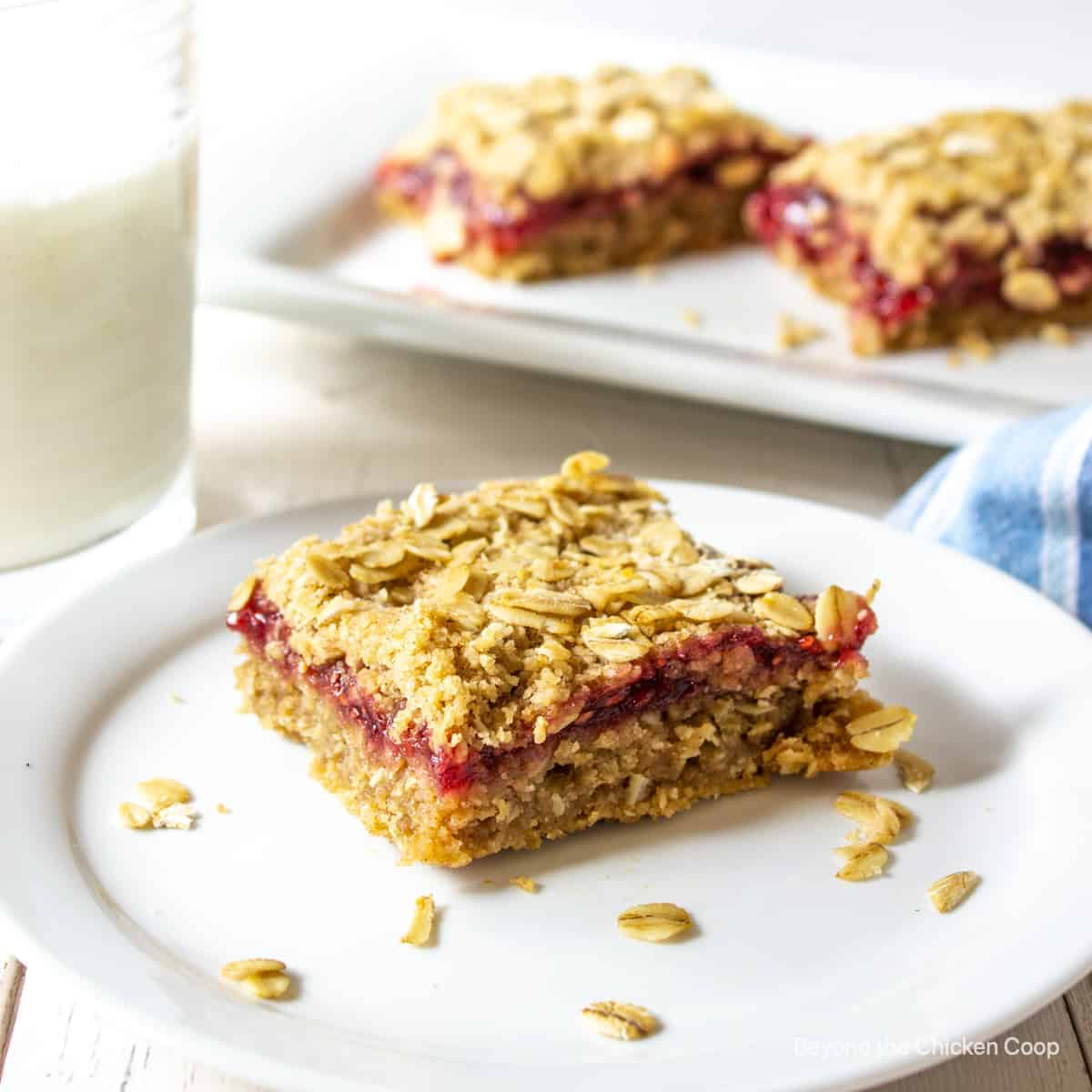 An oatmeal bar filled with raspberry jam on a white plate.