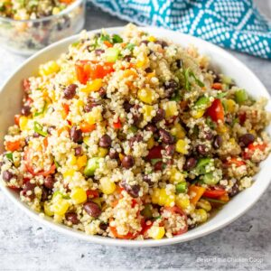 A large white bowl filled with quinoa, black beans, corn and chopped tomatoes.