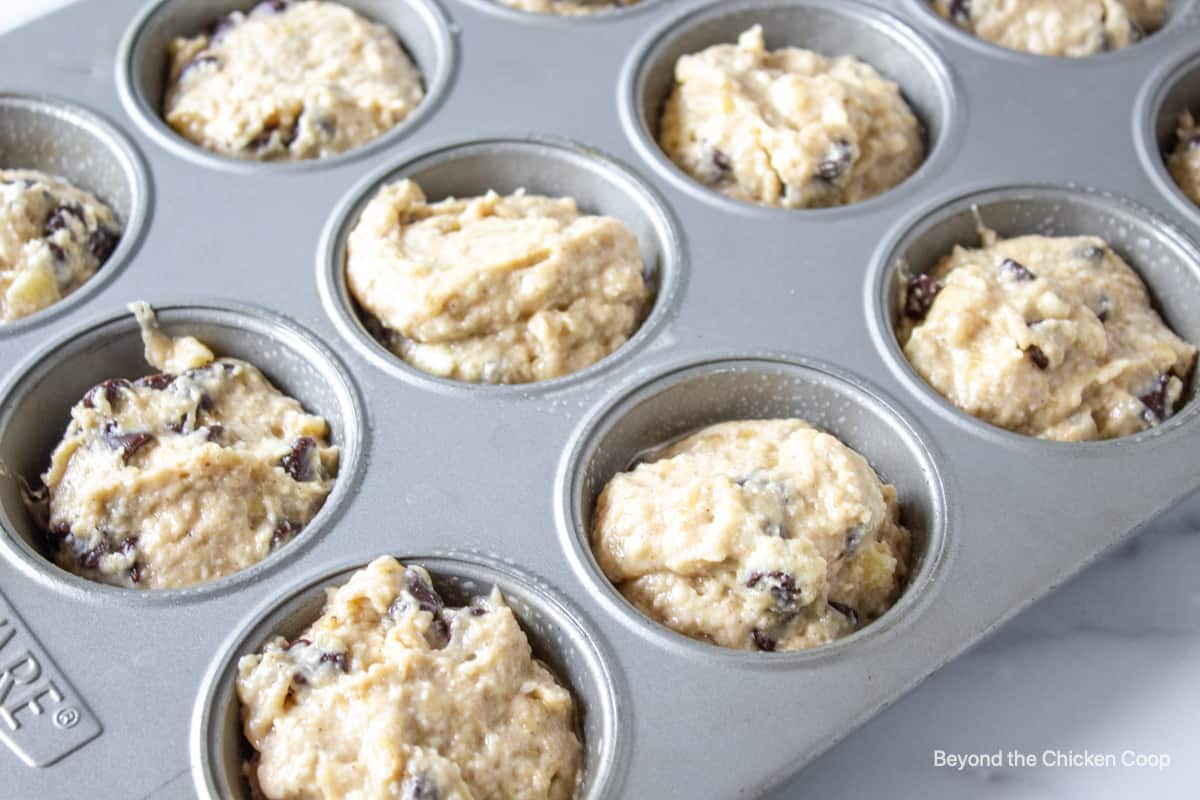 Muffin batter with chocolate chips in muffin tin.