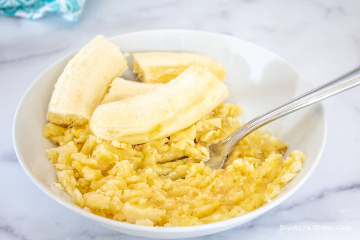 Mashed bananas with a fork in a white bowl.