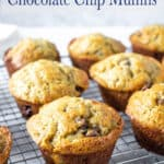 A baking rack filled with muffins with chocolate chips.