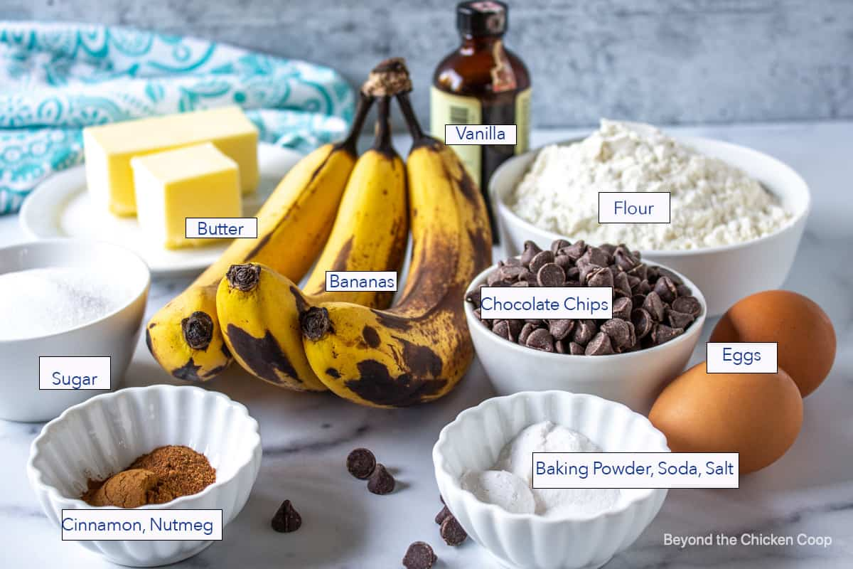 Ripe bananas in the center of small bowls filled with flour, sugar and other ingredients.