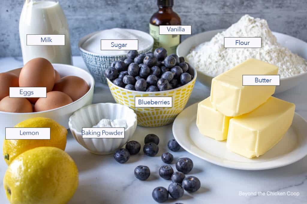 Ingredients for making a cake displayed on a marble surface.
