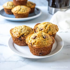 Three muffins on a small white plate.