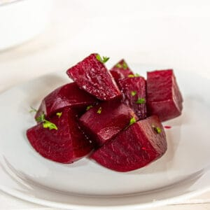 Cubed beets topped with fresh parsley on a white plate.