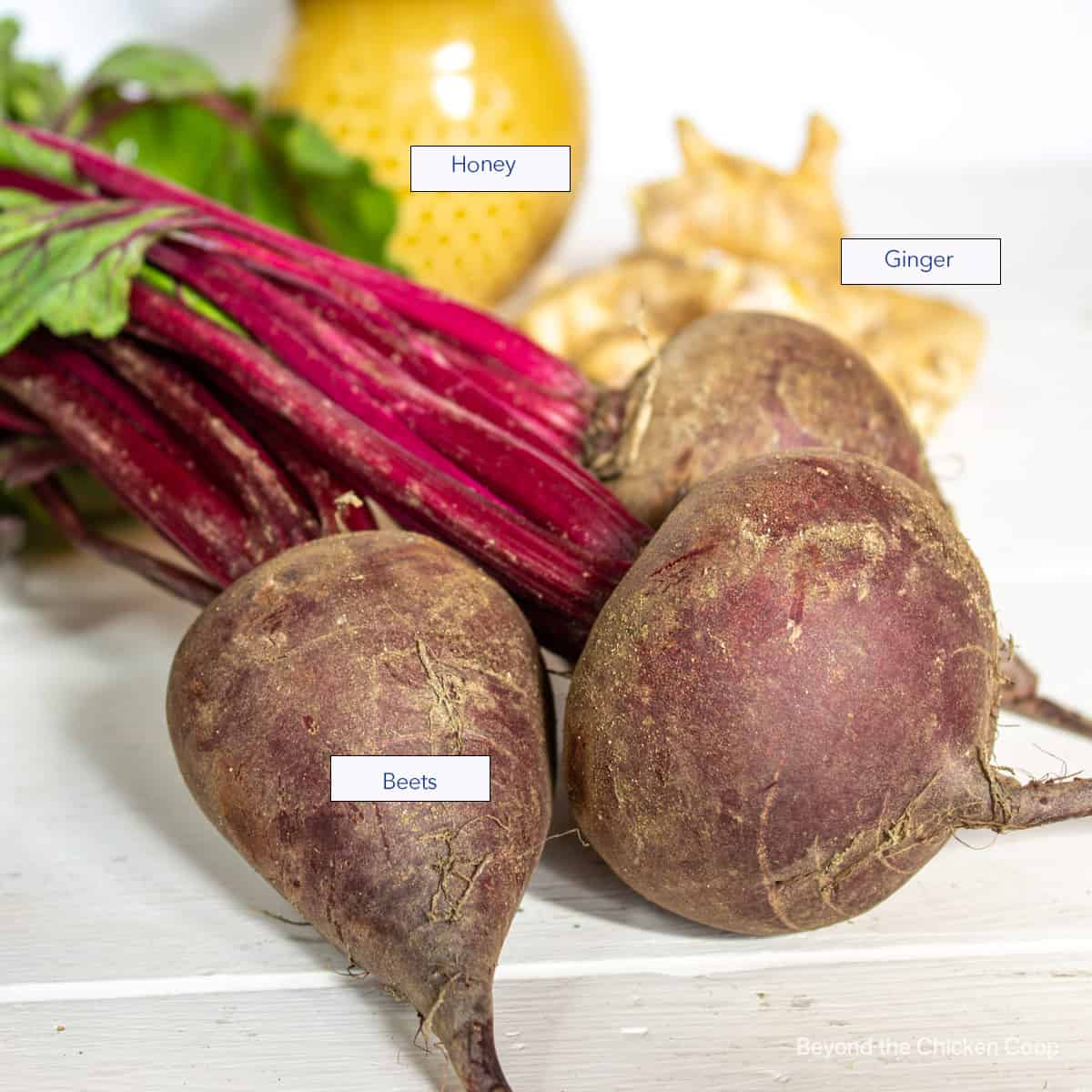 Beets, ginger and honey displayed on a white board.