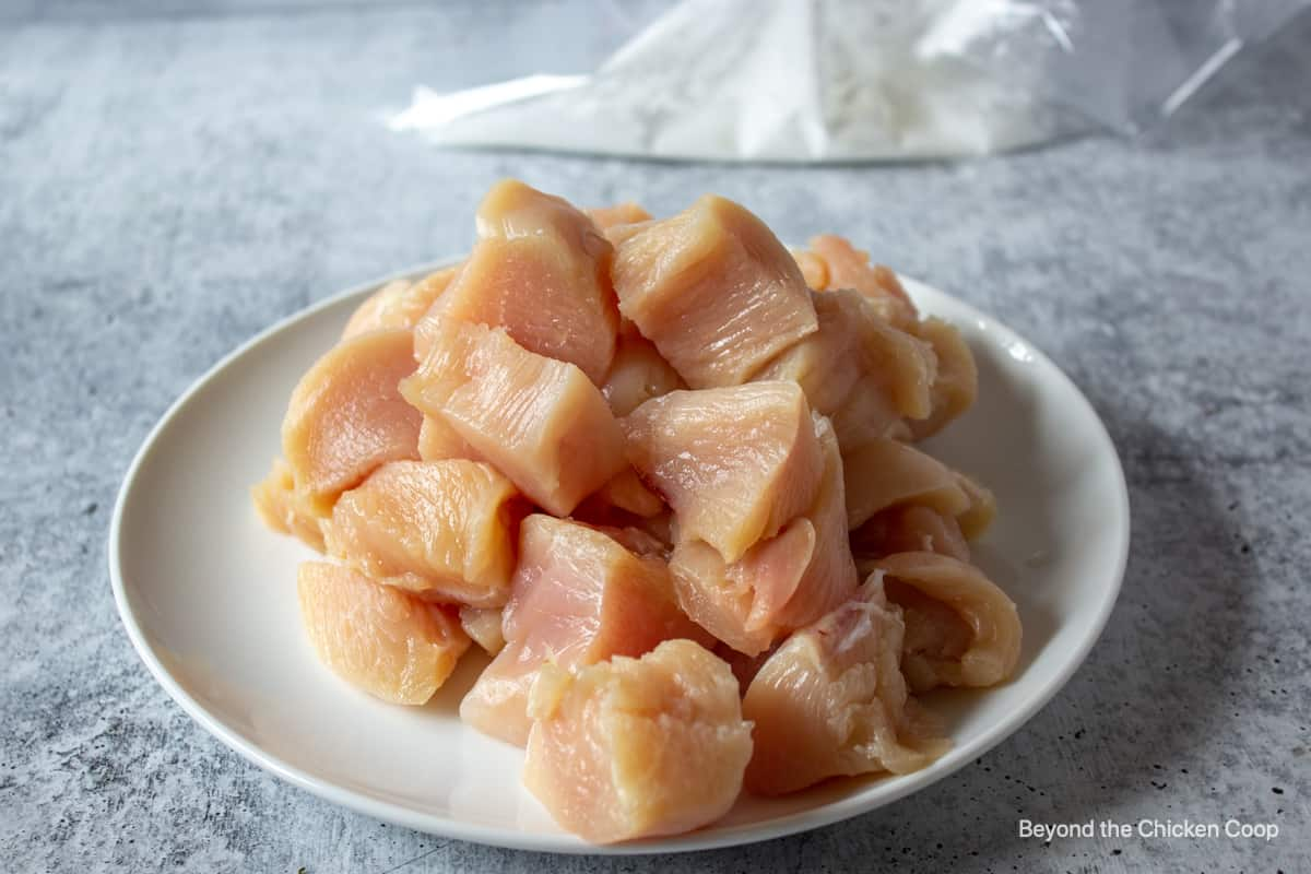 Raw chicken cut up into small cubes.