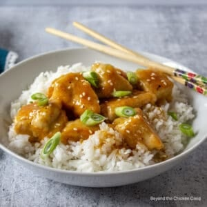A white bowl filled with orange chicken with rice.