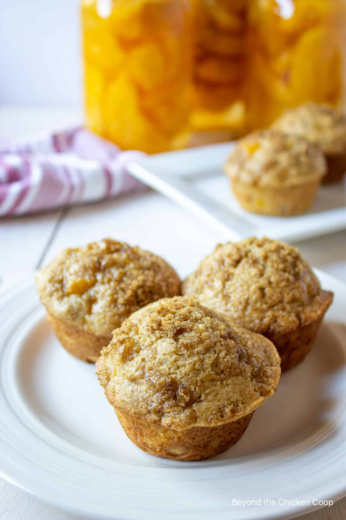 Three muffins with a crumble topping on a white plate.