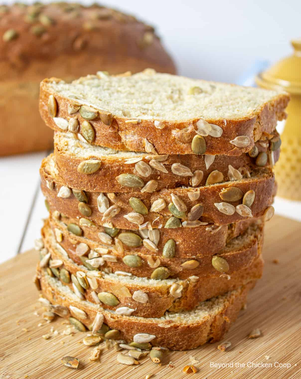 A stack of slice bread studded with pumpkin seeds.