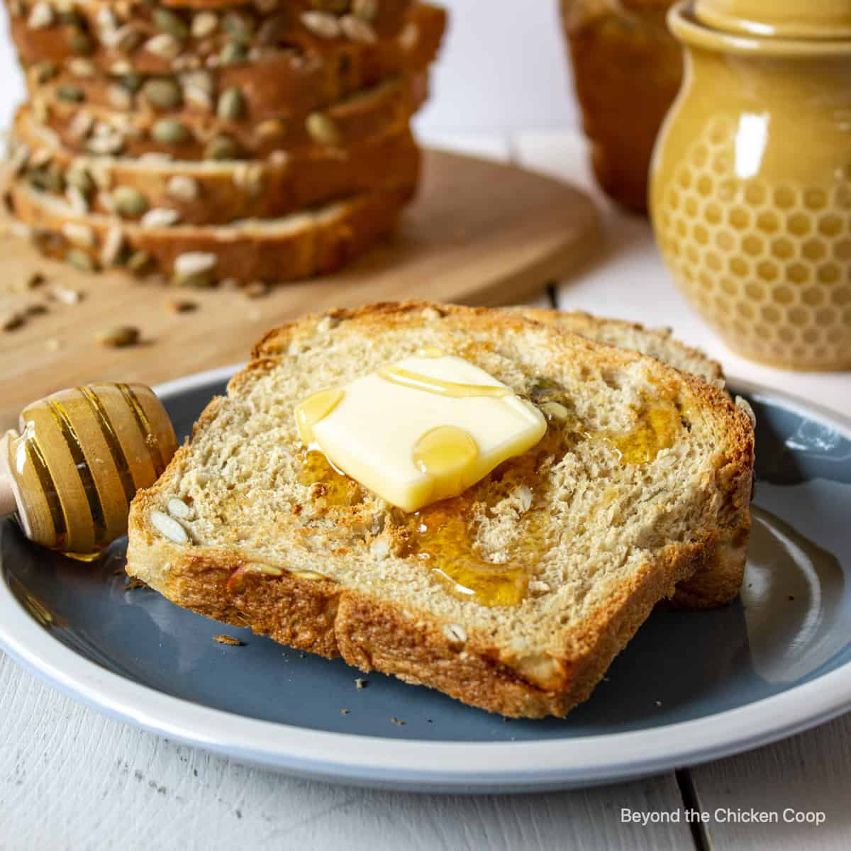 A toasted piece of bread topped with butter and honey.
