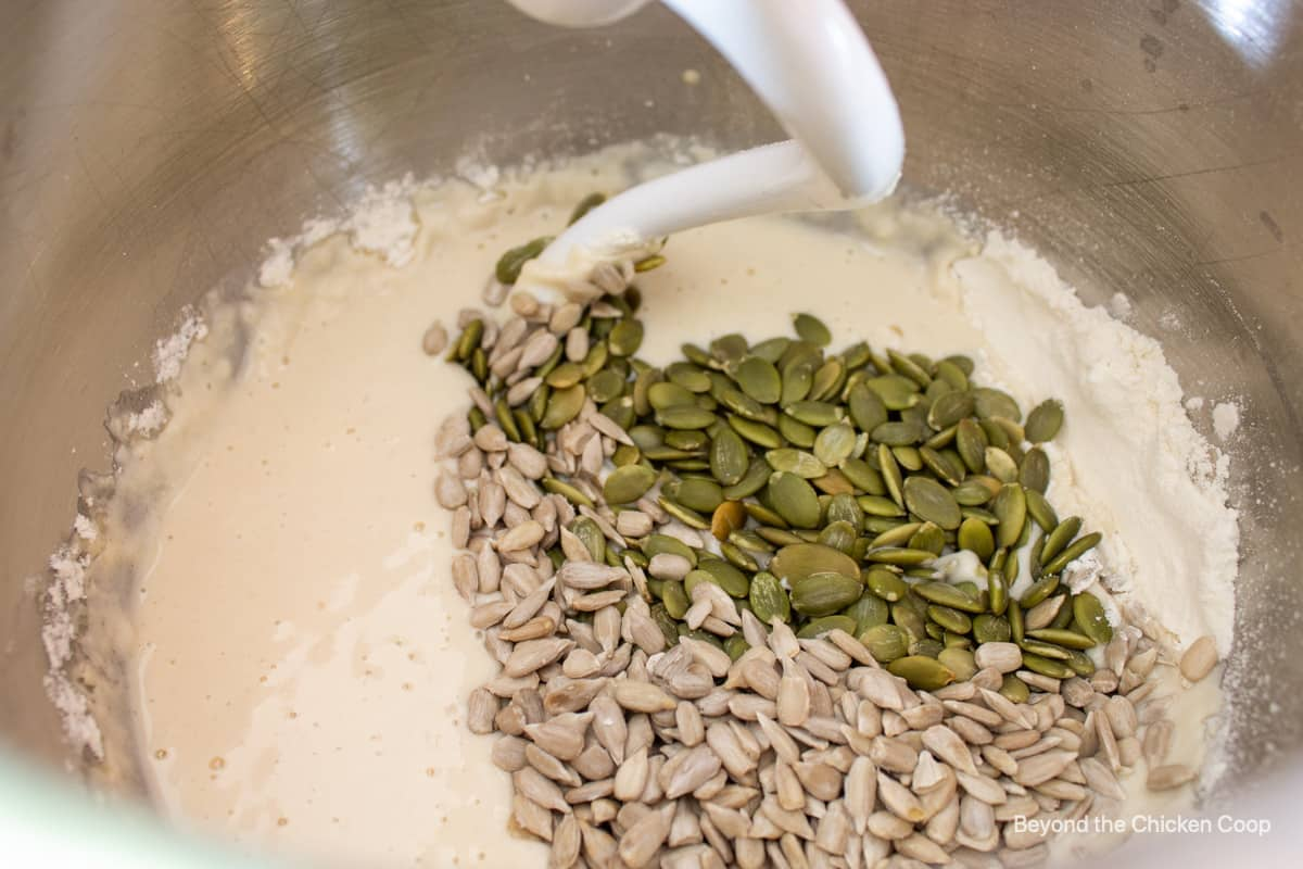 Pumpkin seeds and sunflower seed added to a mixing bowl.
