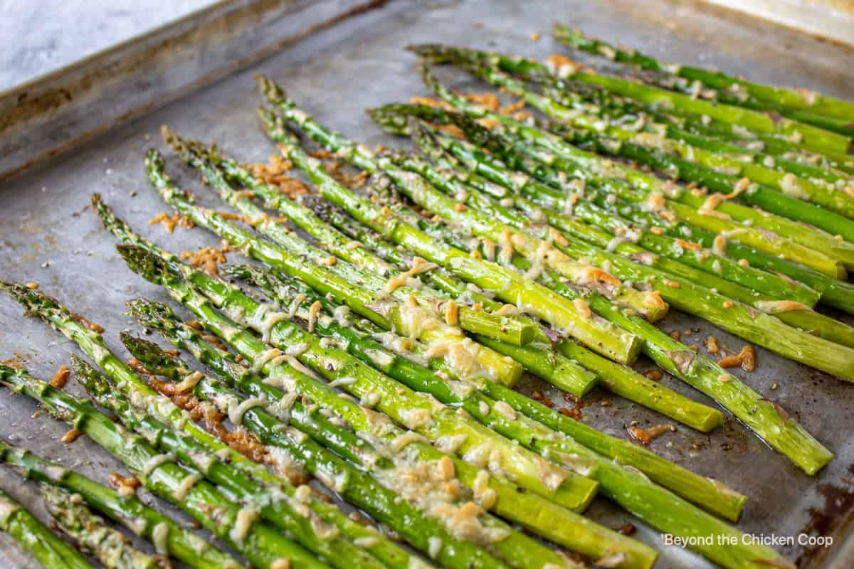 Oven roasted asparagus on a baking sheet.