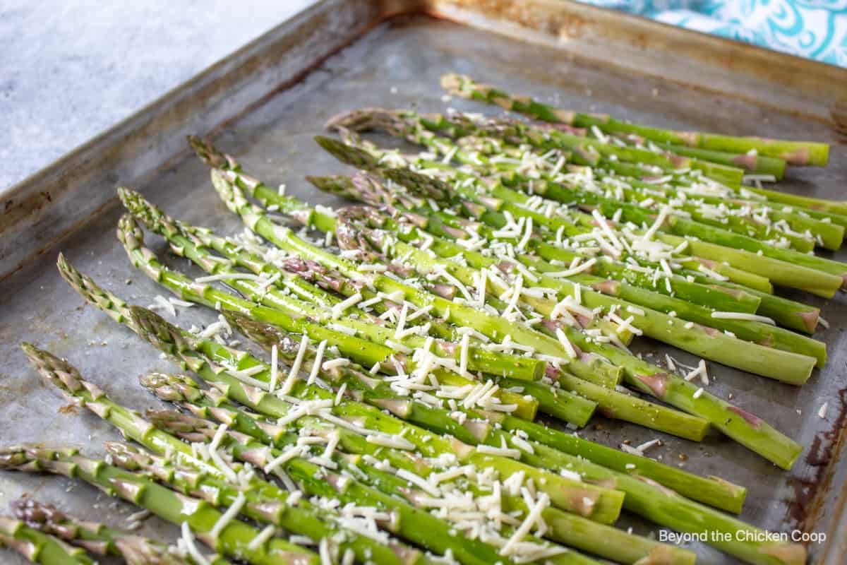 Asparagus topped with parmesan cheese on a baking sheet.