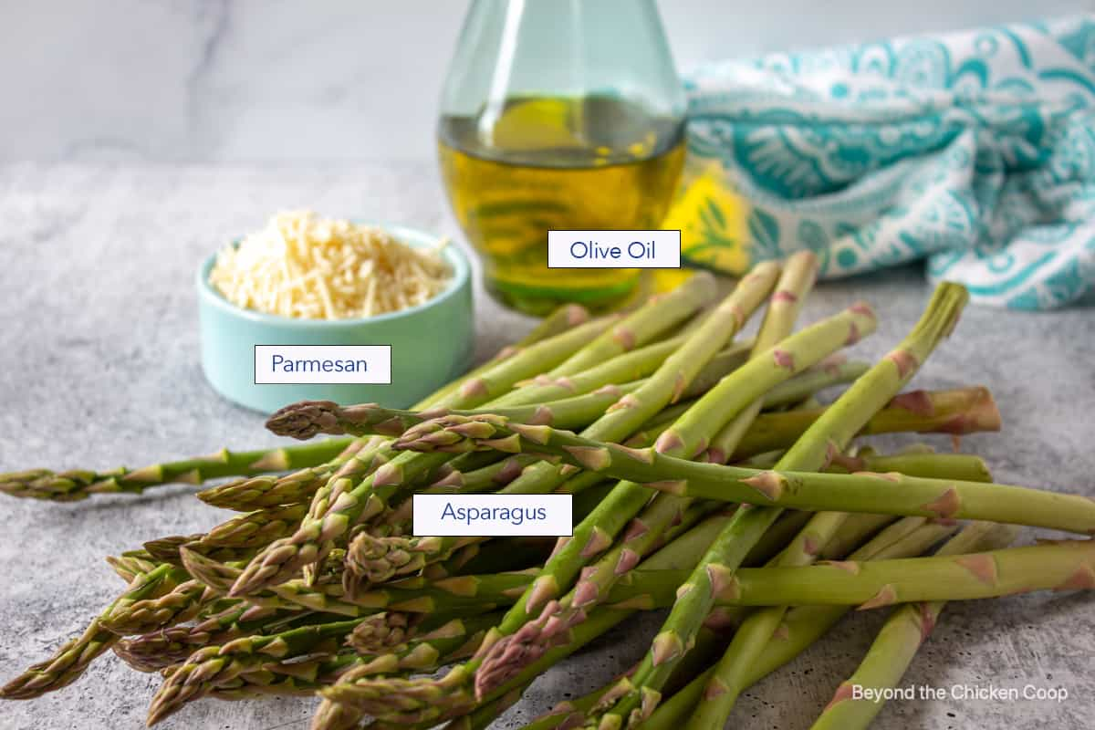 Fresh asparagus on a board with olive oil and parmesan cheese.