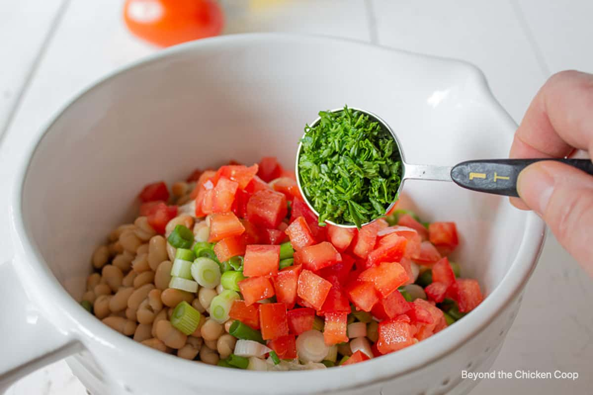 A tablespoon of chopped parsley above a bowl with a bean salad.