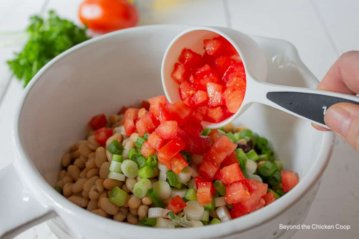 Chopped tomatoes being added to a bowl full of beans.