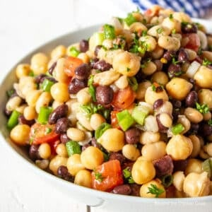 A white bowl filled with a bean salad with tomatoes.