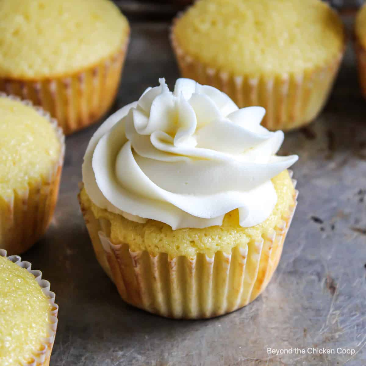A yellow cupcake topped with a swirl of frosting.