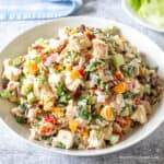 A white dish filled with a colorful chicken salad.
