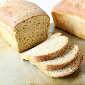 A loaf of home baked bread with three slices cut off the loaf.