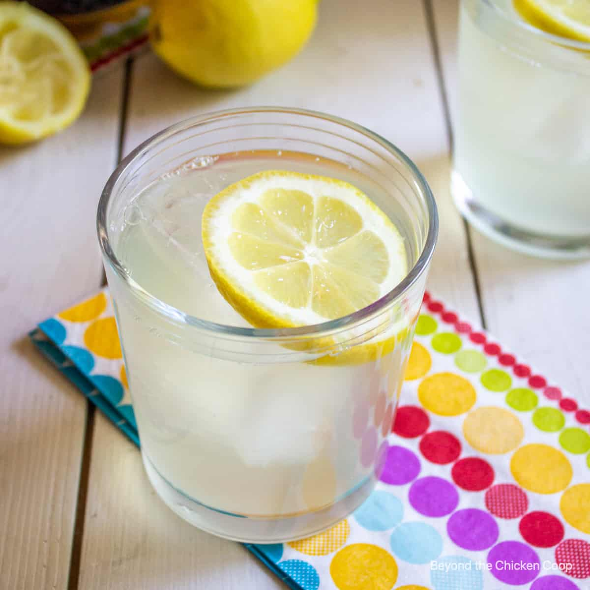 A glass filled with lemonade and a lemon slice.