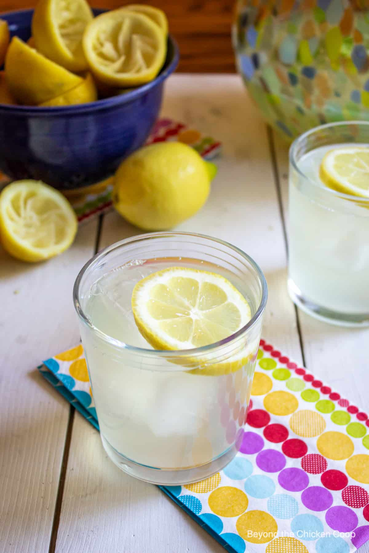 A glass of lemonade and a bowlful of lemons on a white board.