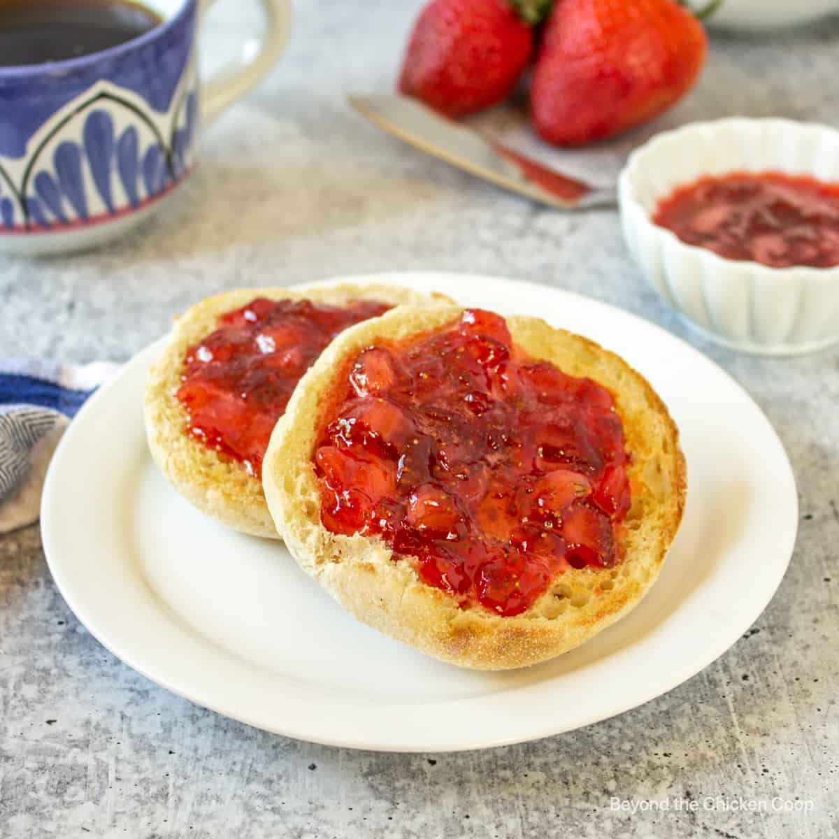 An english muffin topped with chunky strawberry jam.