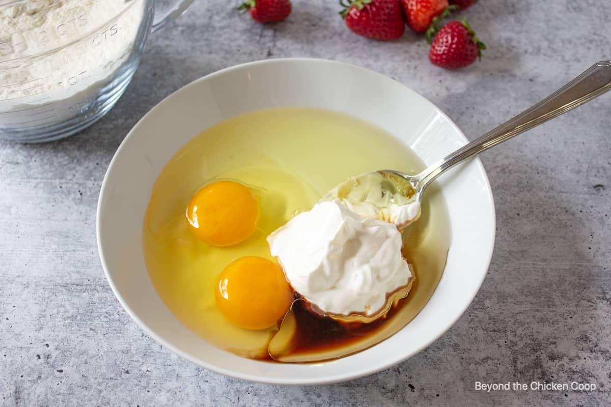 A white bowl with eggs, sour cream, oil and vanilla.