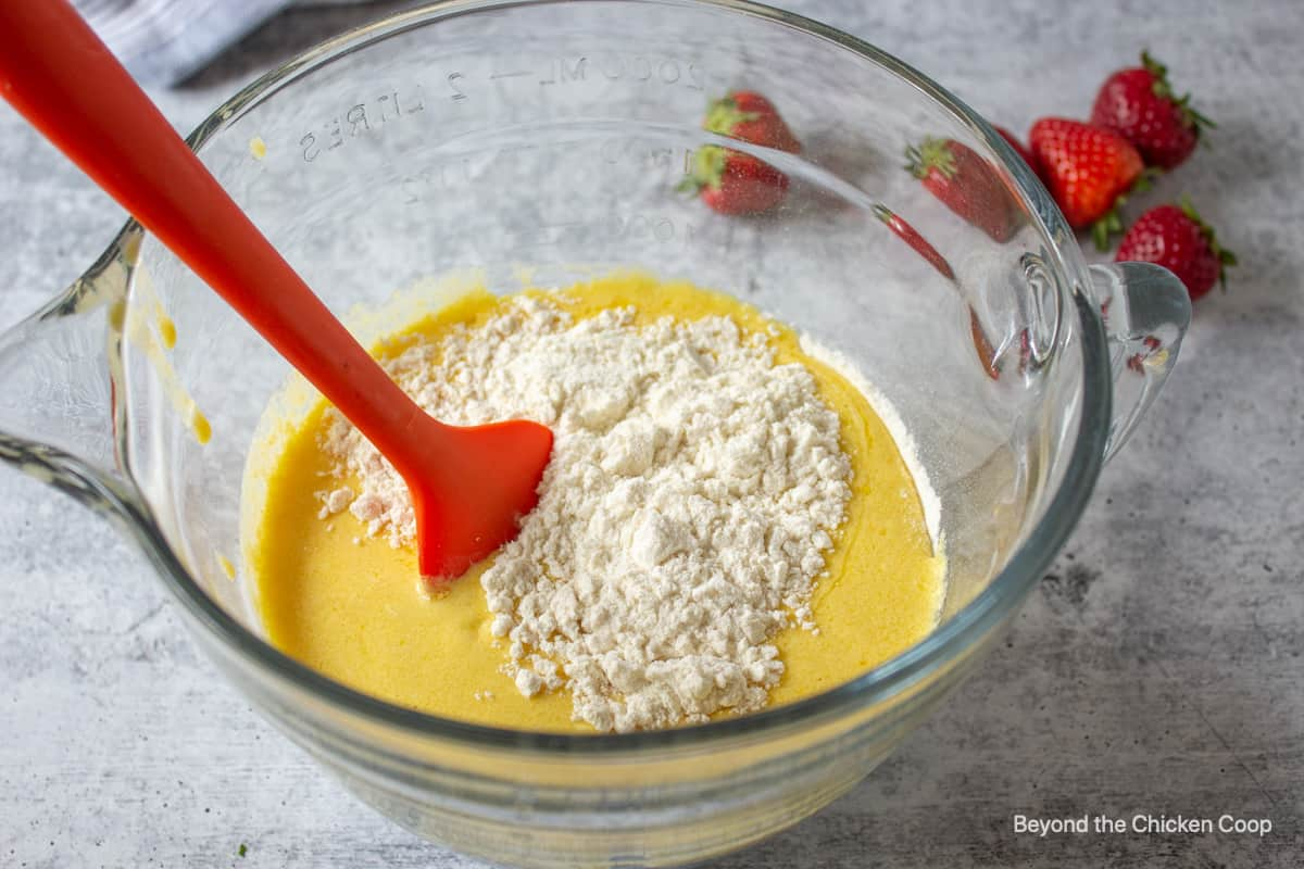 Muffin batter being mixed in a glass bowl with a spatula.